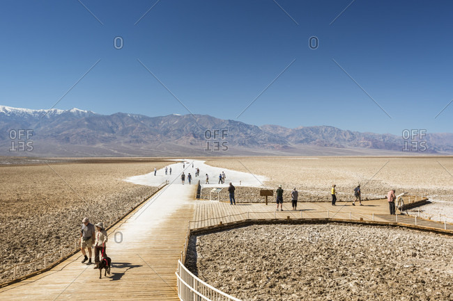 Death Valley, California, USA - July 21, 2017: Tourist walking on badwater basin in death valley national park, california, usa