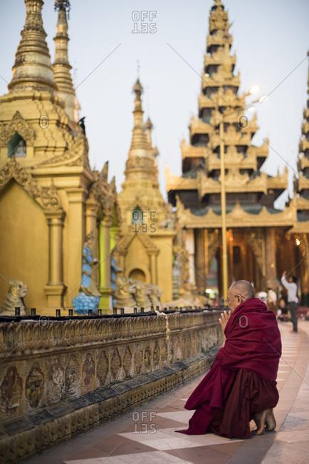 Yangon, Yangon, Myanmar - March 8, 2015: A buddhist monk prays at the shwedagon pagoda, yangon, myanmar.