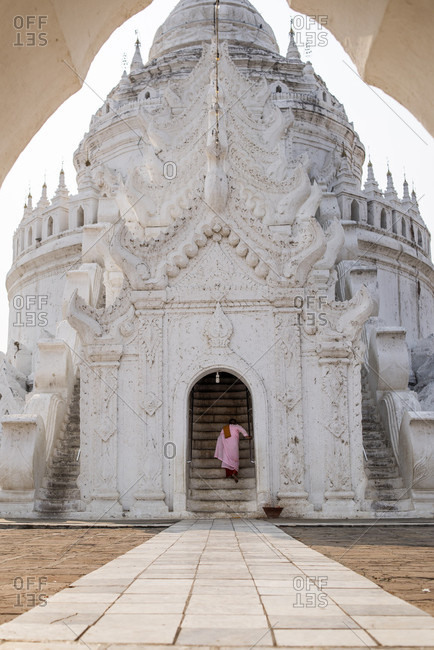 Mingun, Mandalay, Myanmar - March 11, 2015: Buddhist nun climbing staircase of hsinbyume pagoda