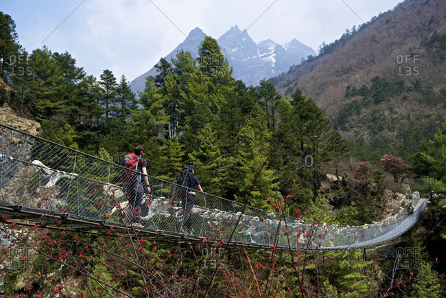 Everest Base Camp Trek, Khumbu, Nepal - August 9, 2016: Climbers crossing a suspension bridge on the way to mount everest base camp