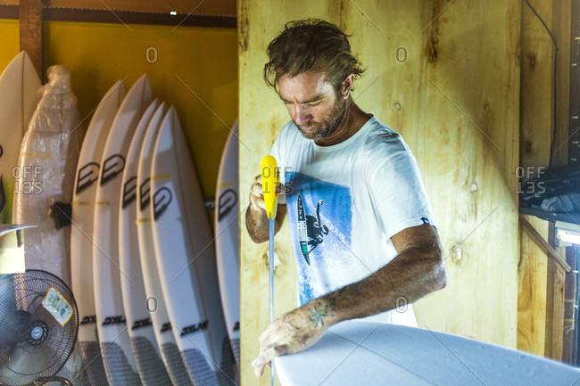 Changgu, Bali, Indonesia - May 3, 2016: Man sawing surfboard to give proper shape to surfboard
