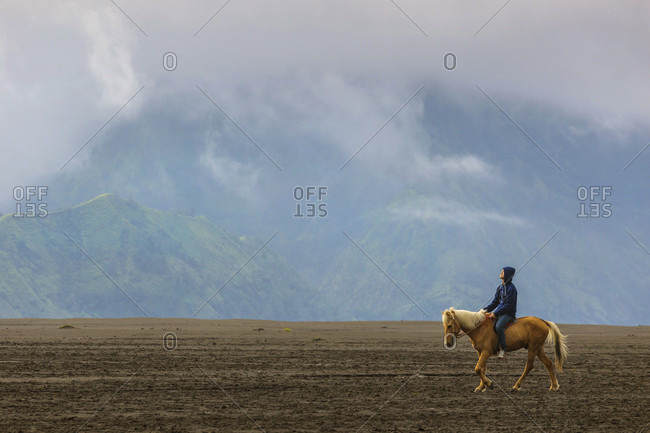 Bromo, Java, Indonesia - June 19, 2016: Horse rider near mount bromo in java, indonesia