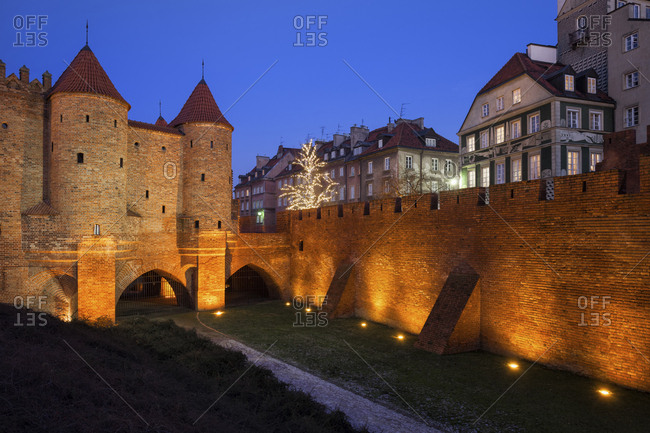 Poland- Warsaw- Old Town at night- illuminated Barbican and city wall