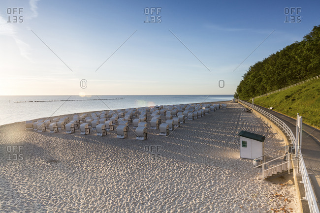 Germany- Ruegen- Sellin- view to beach with hooded beach chairs at morning twilight