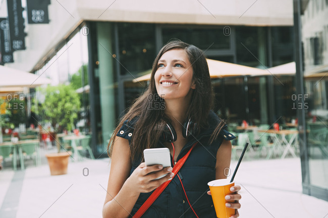 Portrait of smiling young woman with cell phone and takeaway drink in the city