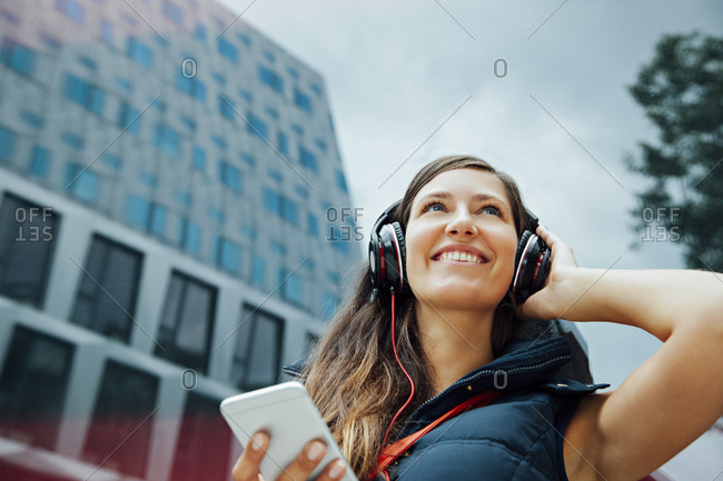 Smiling young woman with headphones and cell phone in the city