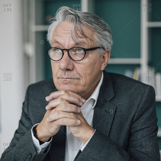 Portrait of senior businessman looking up
