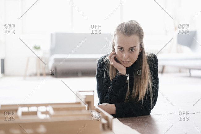 Portrait of blond young woman with architectural model on table