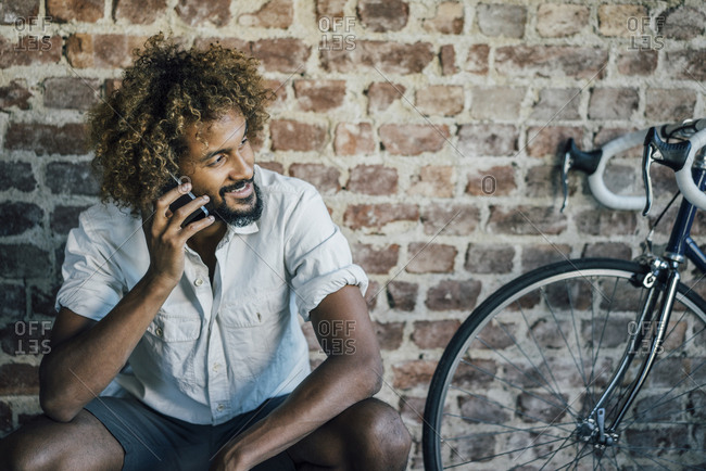 Smiling young man with bicycle on cell phone