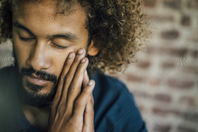 Man with beard and curly hair closing his eyes
