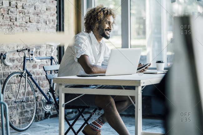 Smiling young man at desk with laptop