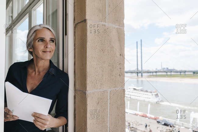 Smiling businesswoman looking out of window in waterfront office