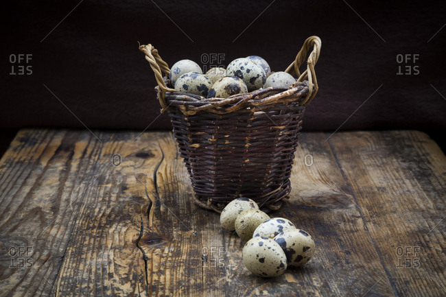 Wicker basket of quail eggs on dark wood