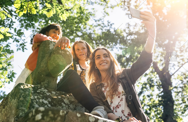 Three happy girls taking a selfie outdoors