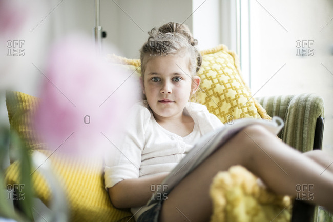 Portrait of relaxed little girl sitting with magazine on armchair