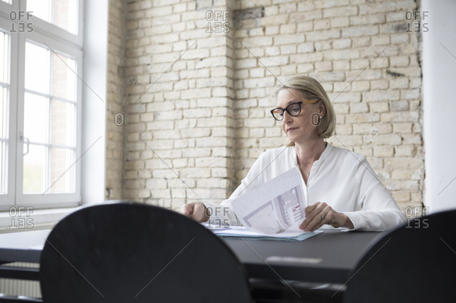 Mature businesswoman working in office- reading documents