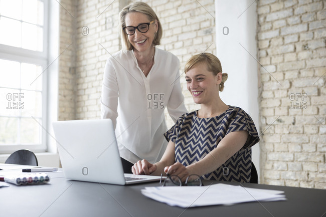 Mature businesswoman working with younger colleague in office