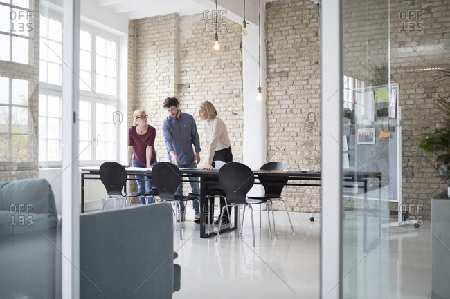 Mature businesswoman working with younger colleagues in office