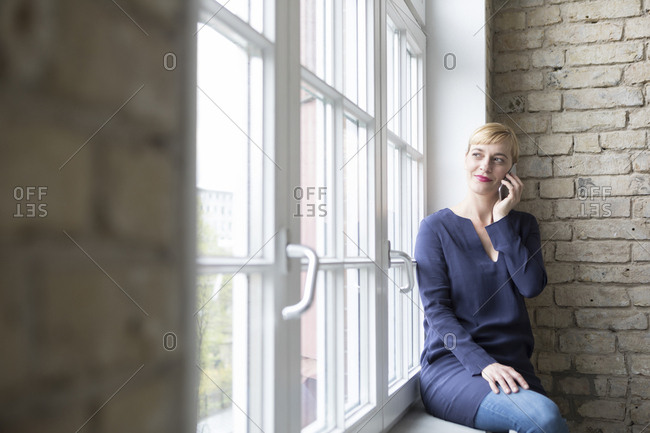 Businesswoman sitting on window sill- making a call