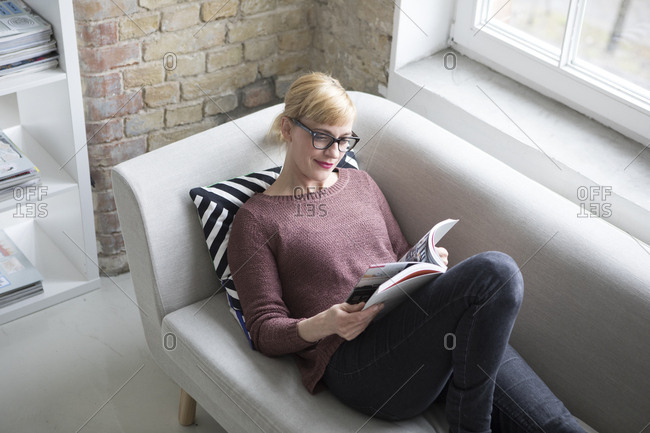 Woman sitting on couch- reading book
