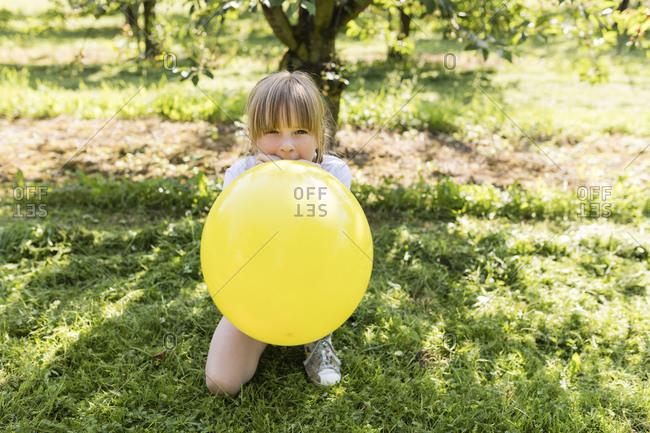 Girl inflating balloon on meadow