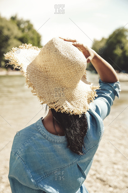Back view of woman wearing straw hat