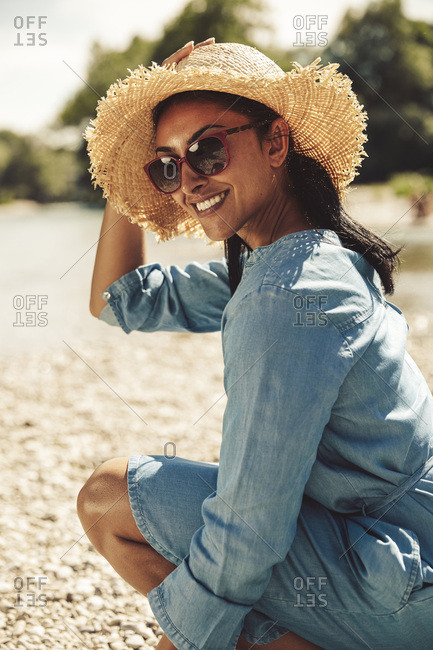 Portrait of happy woman wearing straw hat and sun glasses on the beach