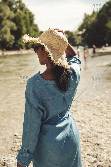 Woman wearing straw hat and jeans dress on the beach