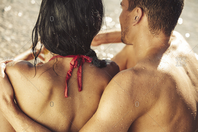 Back view of wet couple on the beach