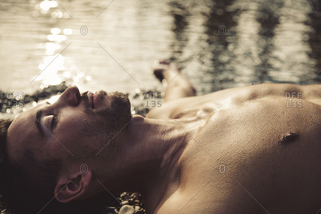 Man relaxing on the beach at sunset