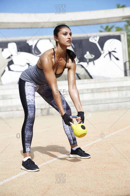 Fit woman exercising with kettle bell outdoors