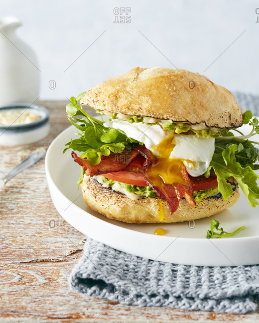 Sandwich with bacon, avocado, poached egg and arugula