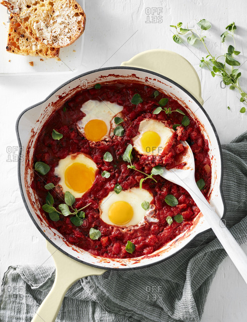 Serving spoon in a pot of shakshuka with tomato sauce and poached eggs