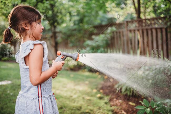 Girl spraying a backyard garden with a water hose