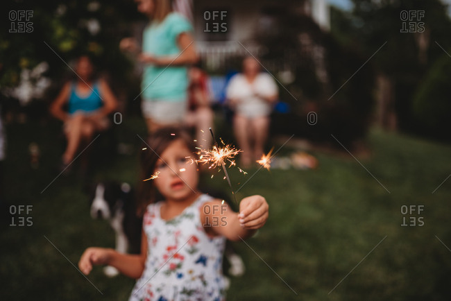 Little girl holding a sparkler outside