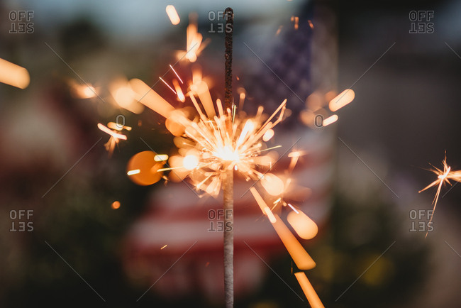 Sparkler glowing in front of an American flag
