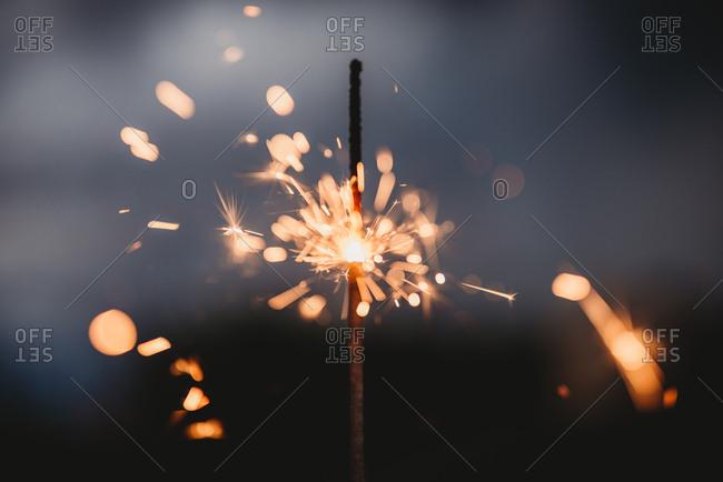 Glowing sparkler burning at twilight