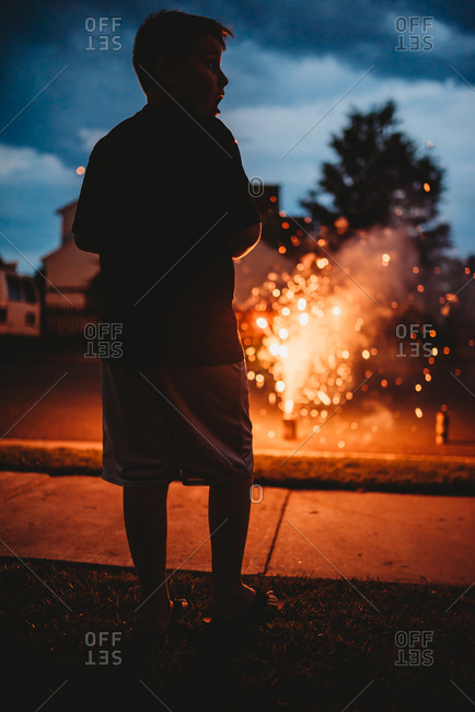 Boy watching fireworks explode in a street at twilight
