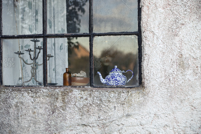 Teapot and candleholder in a window