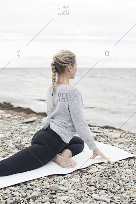 Blonde woman doing yoga on the ocean shore