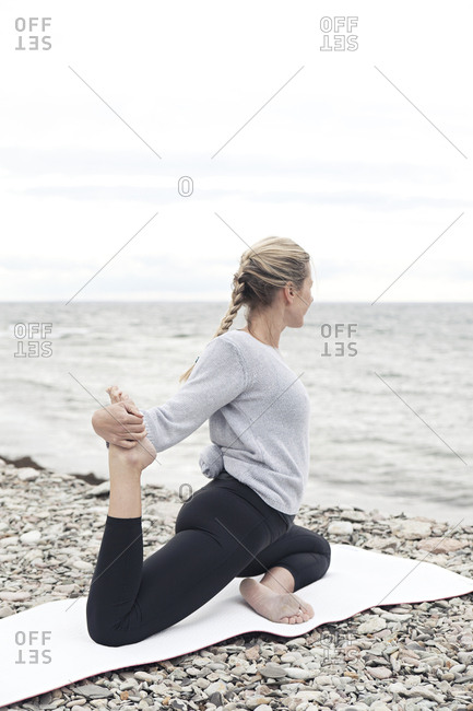 Blonde woman practicing yoga on the ocean shore