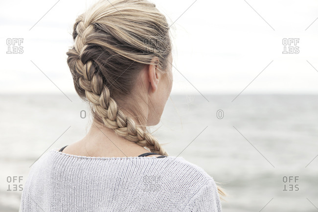 Rear view of blonde woman overlooking the ocean during yoga