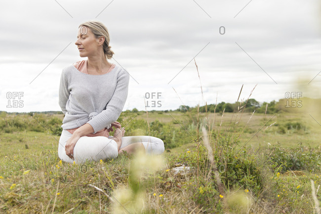 Blonde woman twisting during yoga in a field
