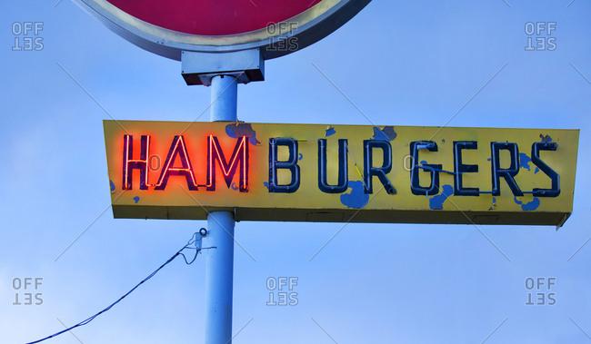 Partially-lit hamburger sign at a roadside restaurant