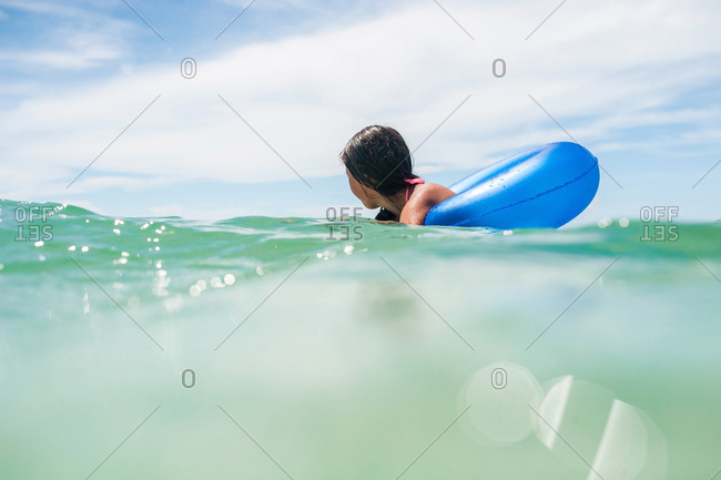 Teen girl in floating tube in ocean
