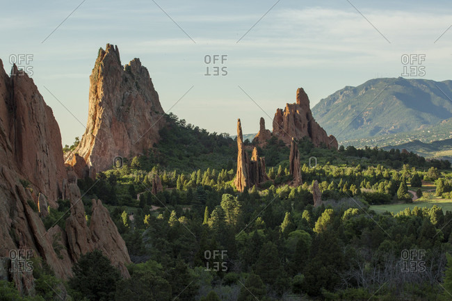 A row of hogbacks or fins protrude from the green trees in Garden of the Gods in Colorado Springs, Colorado.