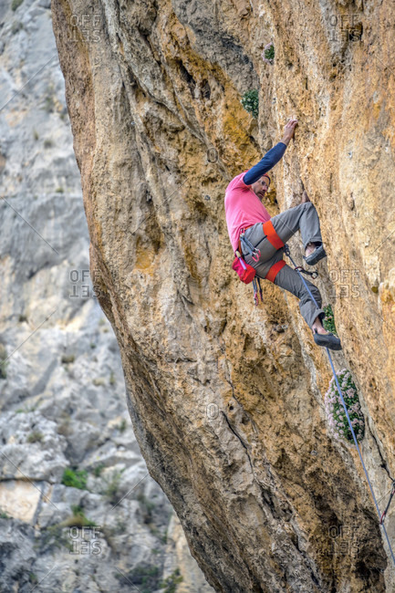 A man climbs a difficult route at La Sombra Leon, Alicante Spain.