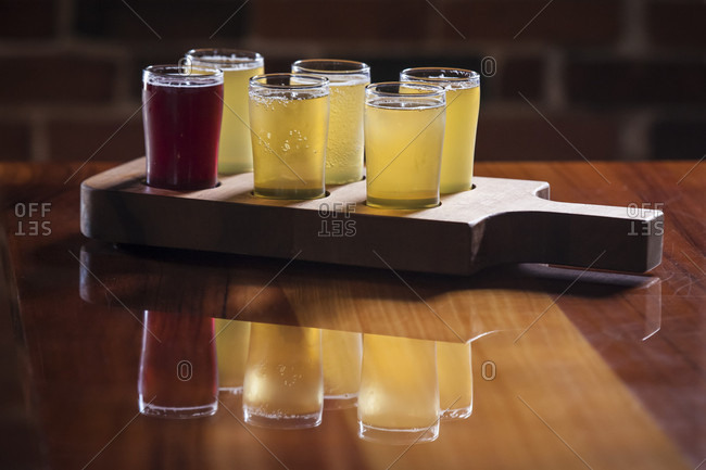 A flight of hard ciders is reflected on a wooden bartop.