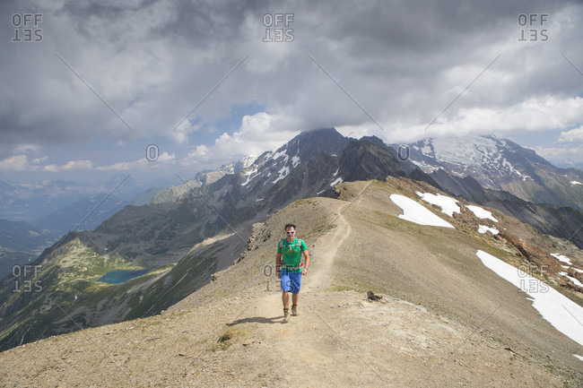 A solo male hiker is walking on the ridge of the Tete des Fours with Mont Blanc in the distance. This is halfway the Tour du Mont Blanc, a classic multi day hike around the highest peak of the Alps.