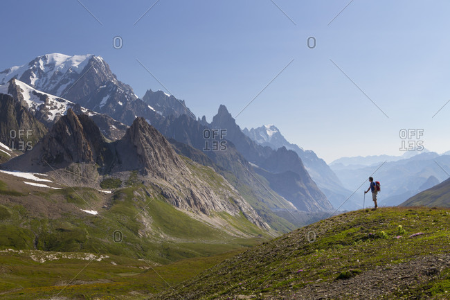 A male hiker is looking over the Val Veny, near Courmayeur, with Mont Blanc dominating the sky line. This is halfway the Tour du Mont Blanc, a classic trekking around the highest peak of the Alps, that goes through France, Italy and Switzerland.